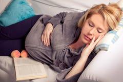 Mujer embarazada que coloca la ventana cercana Foto de archivo libre de regalías