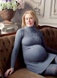 Mujer embarazada que coloca la ventana cercana Fotografía de archivo libre de regalías
