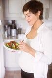 Mujer embarazada que come el cuenco de ensalada Imagenes de archivo
