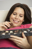 Mujer embarazada que come la caja de chocolates que se sientan en Sofa At Home Imagenes de archivo