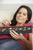 Mujer embarazada que come la caja de chocolates que se sientan en Sofa At Home Fotos de archivo libres de regalías