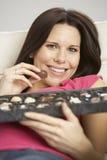 Mujer embarazada que come la caja de chocolates que se sientan en Sofa At Home Fotografía de archivo