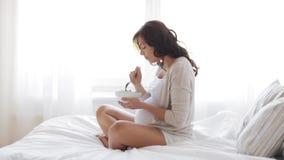 Mujer embarazada que come la ensalada en la cama en casa 43 almacen de video