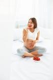 Mujer embarazada que come la fresa en casa Concepto sano del alimento Foto de archivo libre de regalías