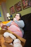 Mujer embarazada que come los anillos de espuma Imágenes de archivo libres de regalías