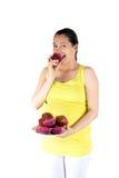 Mujer embarazada que come los molletes Fotos de archivo libres de regalías