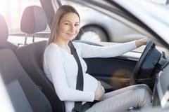 Mujer embarazada que conduce su coche Foto de archivo libre de regalías