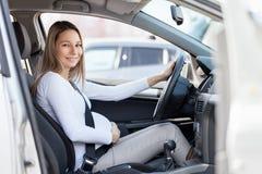 Mujer embarazada que conduce su coche Imagen de archivo libre de regalías