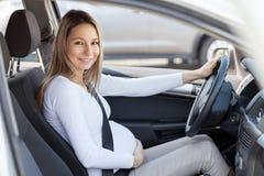 Mujer embarazada que conduce su coche Fotos de archivo libres de regalías