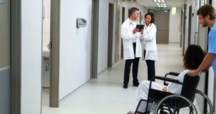 Mujer embarazada que continúa la silla de rueda mientras que doctor que discute en fondo almacen de metraje de vídeo