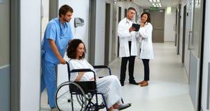 Mujer embarazada que continúa la silla de rueda mientras que doctor que discute en fondo almacen de video