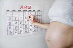 Mujer embarazada que cuenta abajo para la fecha de expedición Imágenes de archivo libres de regalías