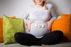 Mujer embarazada que cuenta con a un muchacho fotografía de archivo