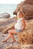 Mujer embarazada que descansa en la playa Imagenes de archivo
