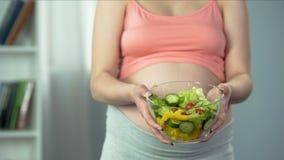 Mujer embarazada que detiene el cuenco de ricos vegetales de la ensalada en vitaminas y alimentos almacen de metraje de vídeo