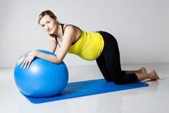 Mujer embarazada que ejercita con la bola de la aptitud Imagen de archivo libre de regalías