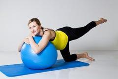 Mujer embarazada que ejercita con la bola de la aptitud Imagenes de archivo