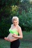 Mujer embarazada que ejercita con las pesas de gimnasia al aire libre Imagen de archivo libre de regalías