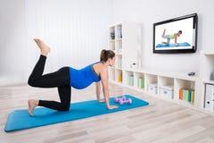 Mujer embarazada que ejercita mirando la televisión fotos de archivo