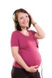 Mujer embarazada que escucha la música Fotografía de archivo