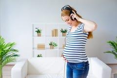 Mujer embarazada que escucha la música Imagen de archivo