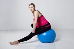 Mujer embarazada que estira con la bola de la aptitud Fotos de archivo libres de regalías