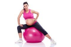 Mujer embarazada que estira las piernas Imágenes de archivo libres de regalías