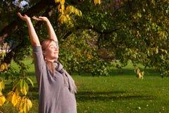Mujer embarazada que estira temprano por la mañana al aire libre Perfil de alcanzar femenino expectante joven para el sol Disfrut foto de archivo