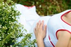 Mujer embarazada que frota ligeramente su vientre en la hierba en un campo con las flores blancas El concepto de una nueva vida imagen de archivo
