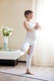 Mujer embarazada que hace actitud de la yoga del árbol en casa Fotos de archivo libres de regalías
