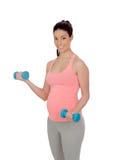 Mujer embarazada que hace ejercicio con pesas de gimnasia Imágenes de archivo libres de regalías