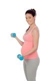 Mujer embarazada que hace ejercicio con pesas de gimnasia Fotos de archivo libres de regalías