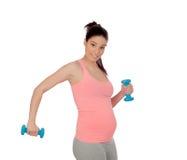 Mujer embarazada que hace ejercicio con pesas de gimnasia Imagen de archivo libre de regalías