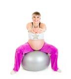 Mujer embarazada que hace ejercicios en bola de la aptitud Foto de archivo libre de regalías