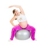 Mujer embarazada que hace ejercicios en bola de la aptitud Fotografía de archivo libre de regalías