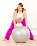 Mujer embarazada que hace ejercicios en bola de la aptitud Fotos de archivo libres de regalías