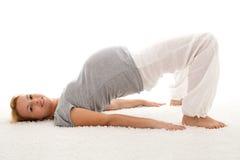 Mujer embarazada que hace ejercicios en el suelo Foto de archivo libre de regalías
