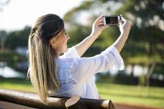Mujer embarazada que hace el autorretrato usando smartphone Fotos de archivo