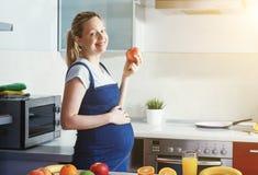 Mujer embarazada que hace el zumo de fruta sano y que come la manzana Imagen de archivo