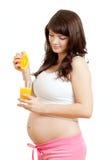 Mujer embarazada que hace el zumo de naranja fresco imagen de archivo libre de regalías