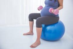 Mujer embarazada que hace exersice en una bola de la yoga, sosteniendo el barbell adentro Imágenes de archivo libres de regalías
