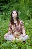 Mujer embarazada que hace la yoga meditating imagenes de archivo