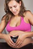 Mujer embarazada que hace un corazón sobre el ultrasonido Imagen de archivo libre de regalías