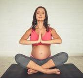 Mujer embarazada que hace yoga Fotografía de archivo