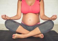 Mujer embarazada que hace yoga Imagen de archivo