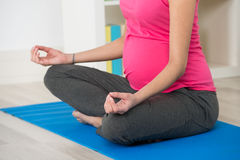 Mujer embarazada que hace yoga en la estera del ejercicio en casa fotos de archivo libres de regalías