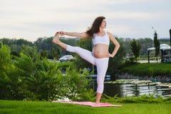 Mujer embarazada que hace yoga prenatal en la naturaleza fotos de archivo libres de regalías