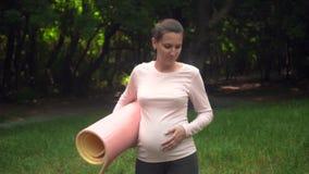 Mujer embarazada que hace yoga Una muchacha camina con una manta en su mano, después lanzar la manta en la hierba de comenzar a p almacen de video