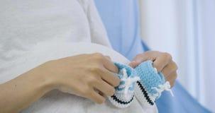 Mujer embarazada que juega con pocos zapatos en su vientre para el bebé nonato en cama metrajes