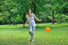 Mujer embarazada que juega a fútbol Imagen de archivo libre de regalías